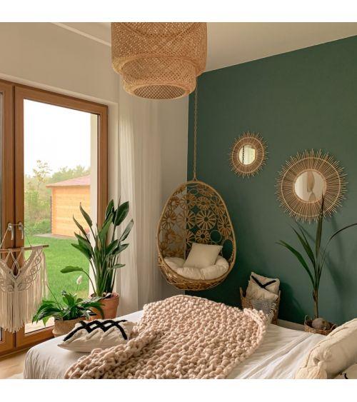 Fotel wiszący do salonu - rattanowy kokon w kolorze beżowym.
